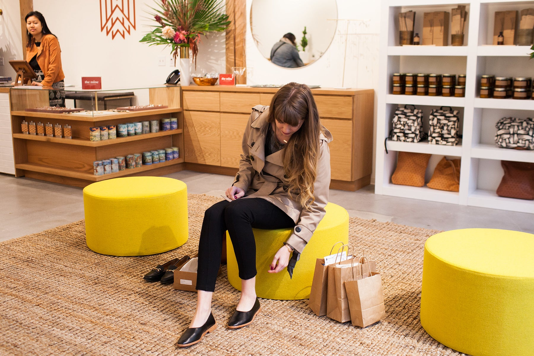 Image of a store interior. A woman in the foreground sits on a round yellow stool trying on shoes