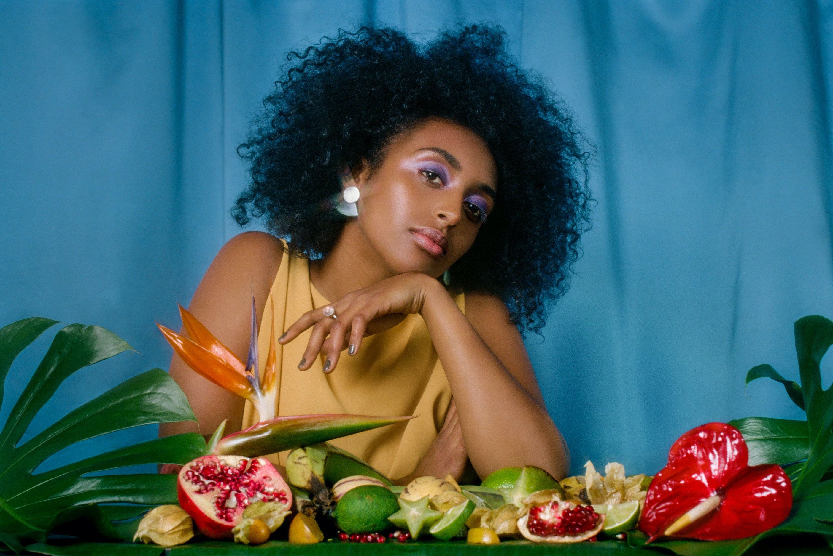 Woman wearing jewelry sits at a table covered in fruit