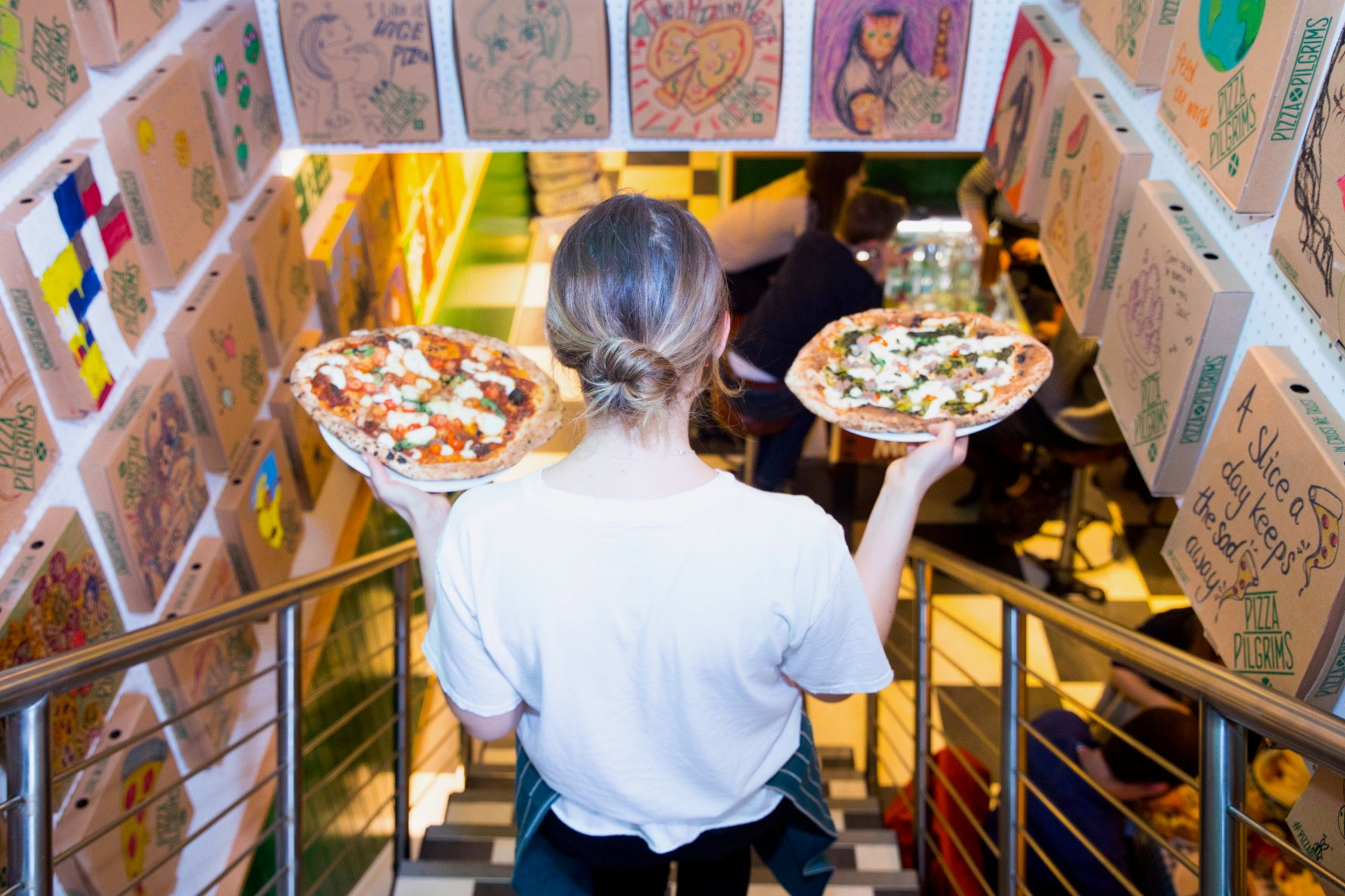 A waitress with two pizzas in her hands at the Shoreditch location of Pizza Pilgrims back in its bustling days prior to COVID-19