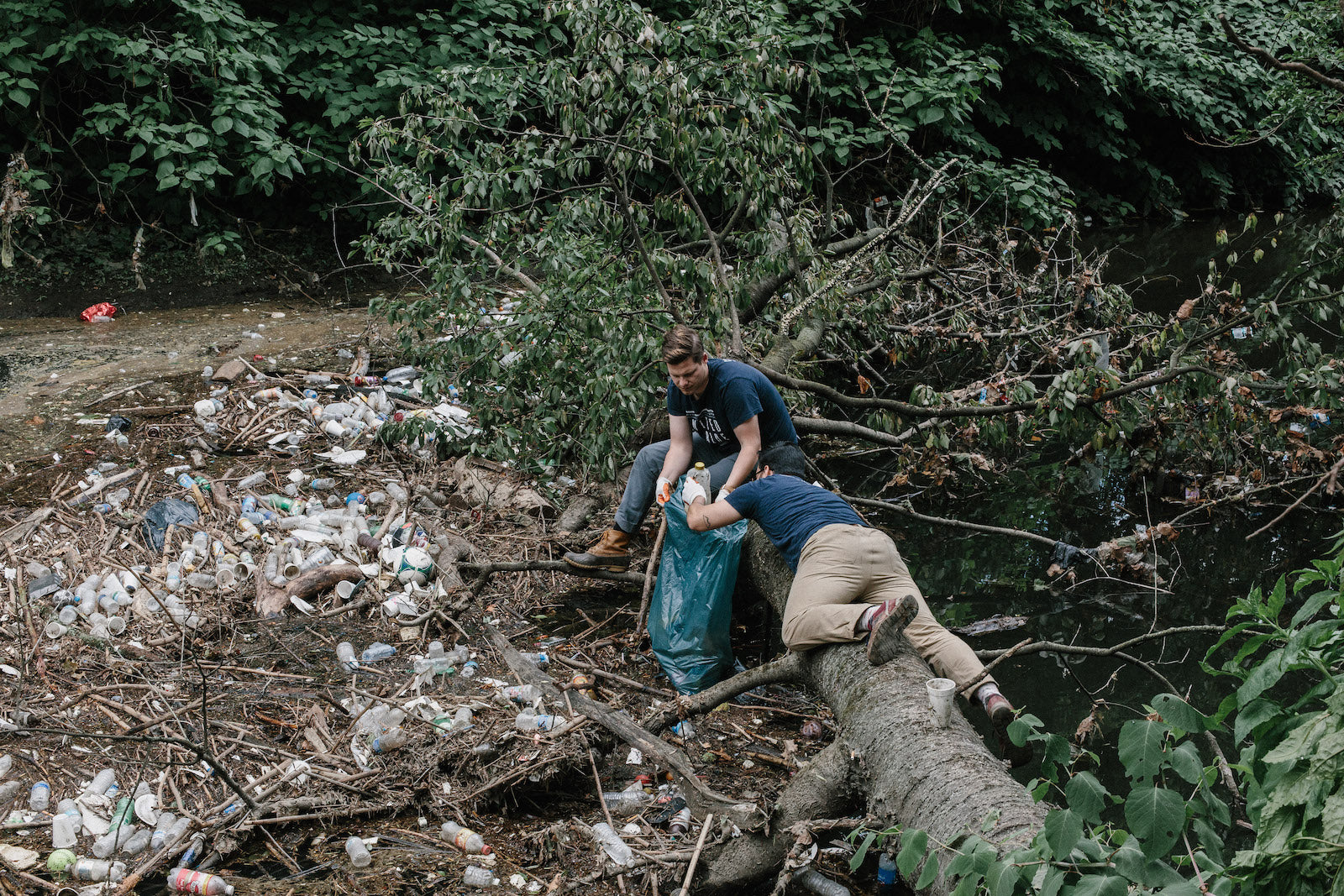 United By Blue co-founders Bryan and Mike collect trash from a riverside in their home city of Philadelphia.