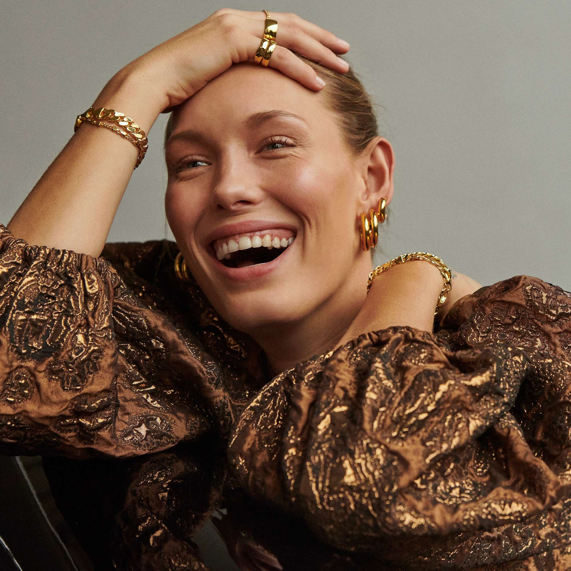 A model in a gold dress smiling and wearing multiple pieces of earrings, rings, and bracelets from Camille Brinch.