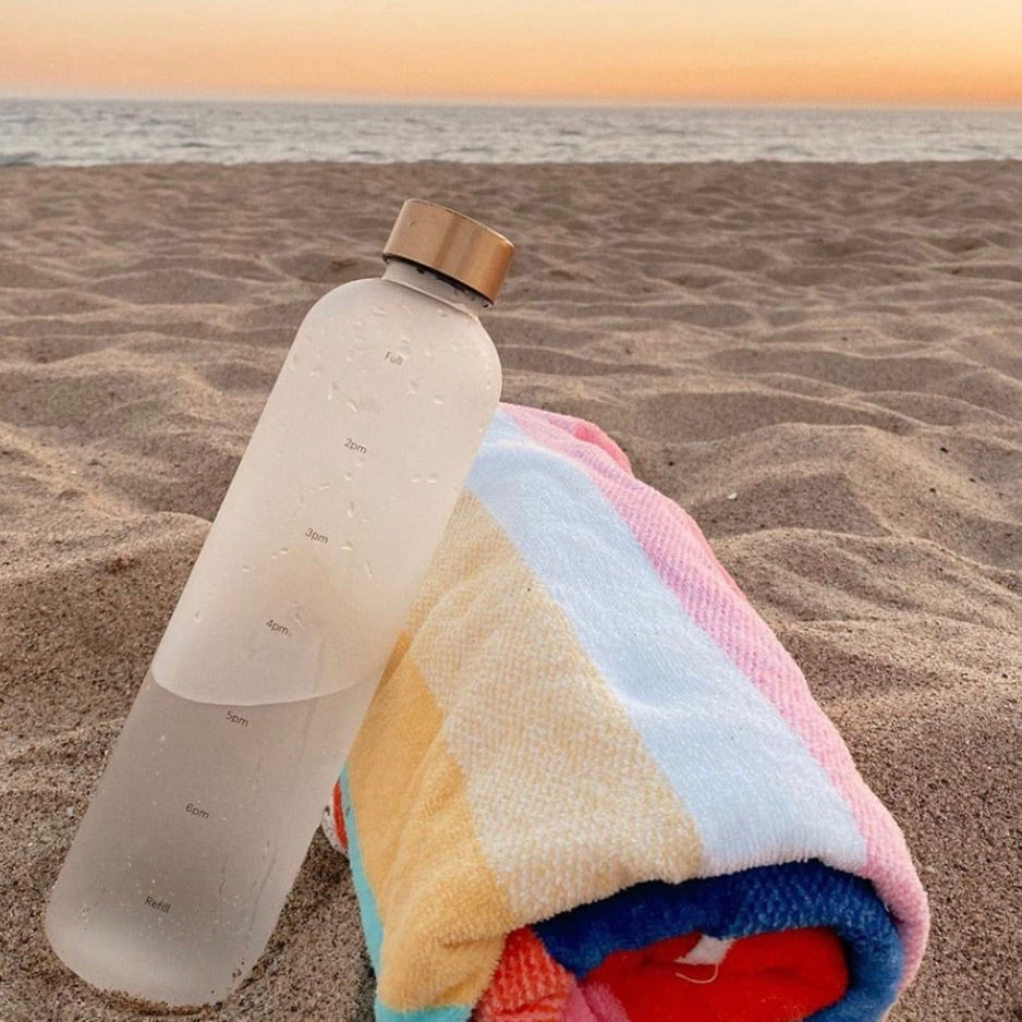 A water bottle by Healthish on the beach next to a beach towel.