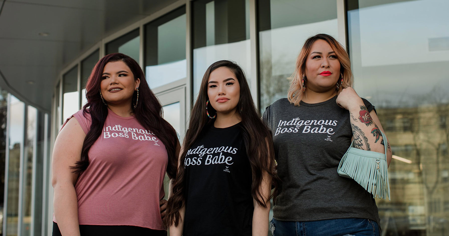 Photograph of three Indigenous women wearing t-shirts that read Indigenous Boss Babe created by the brand SheNative