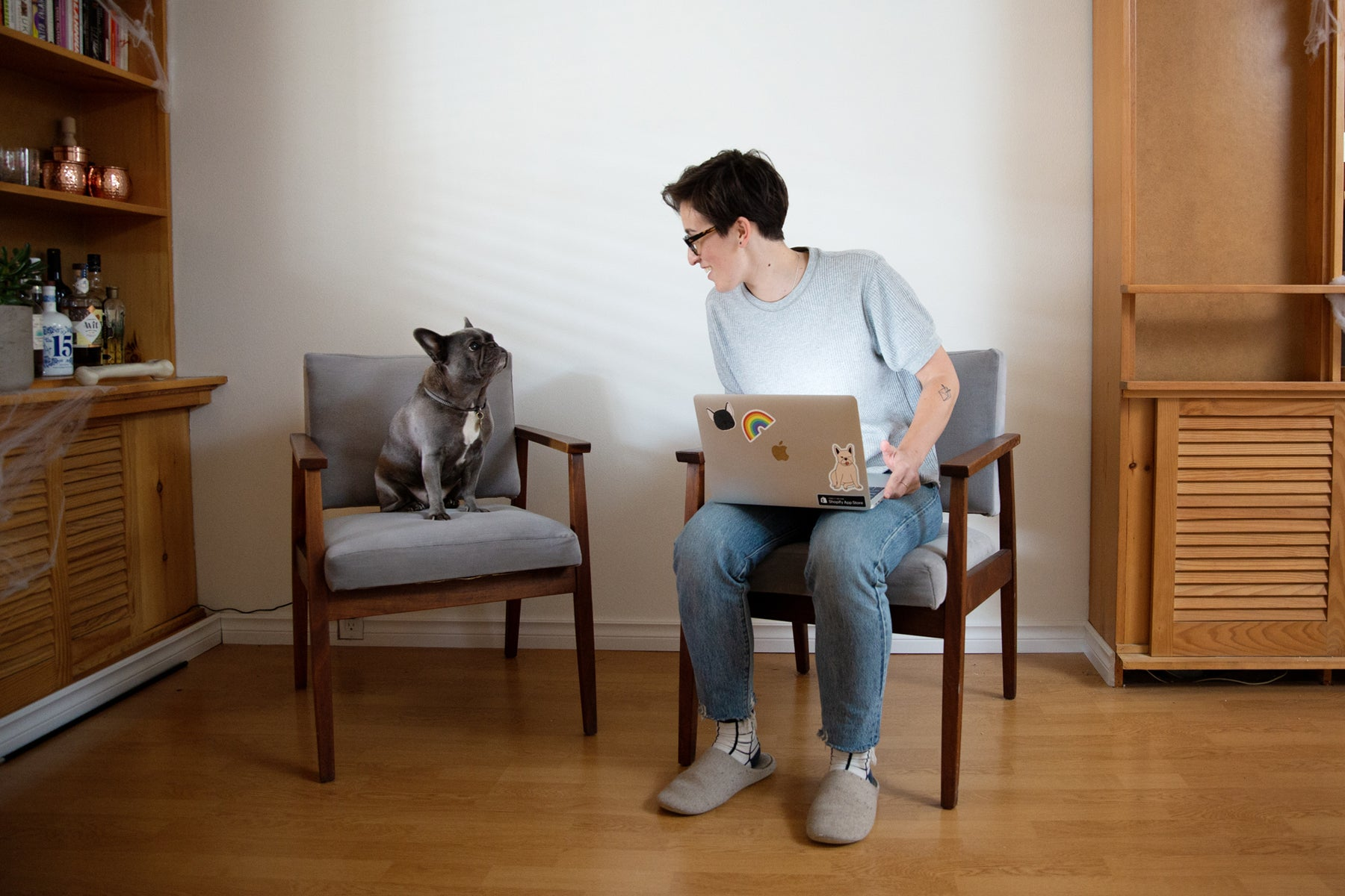 Passionfruit founder Liz Bertorelli sits with her laptop. Her french bulldog Olive sits beside her.