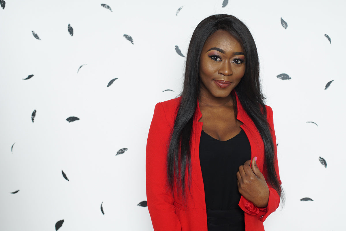 Bili Boboe-Balogun, the founder of Tribe Beauty Box wearing a red blazer, in front of a white and grey background