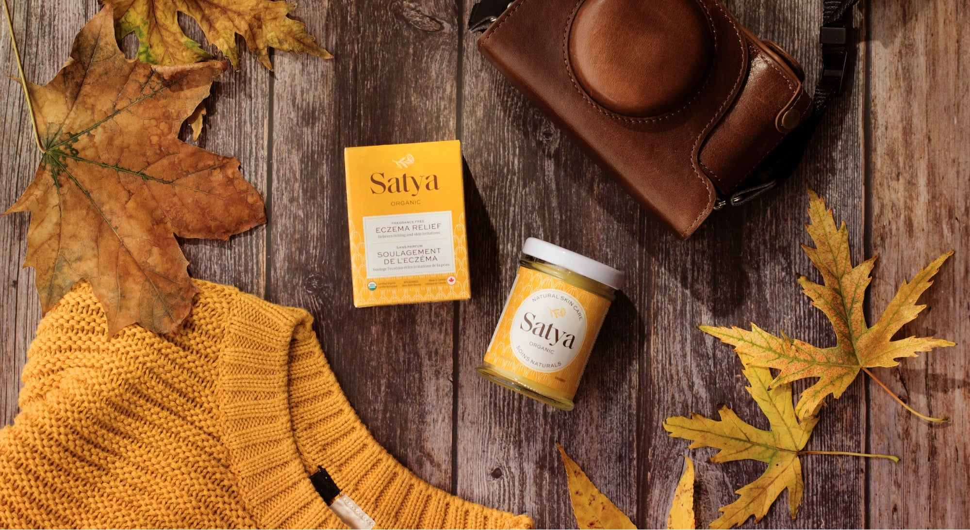 a flatlay of Satya products against a rustic, automnal backdrop featuring leaves, a camera and a yellow sweater