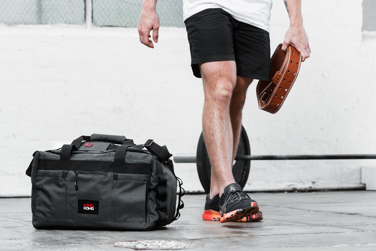 A male model in shorts and running shoes standing next to a duffle bag designed by King Kong Apparel specifically for CrossFit.