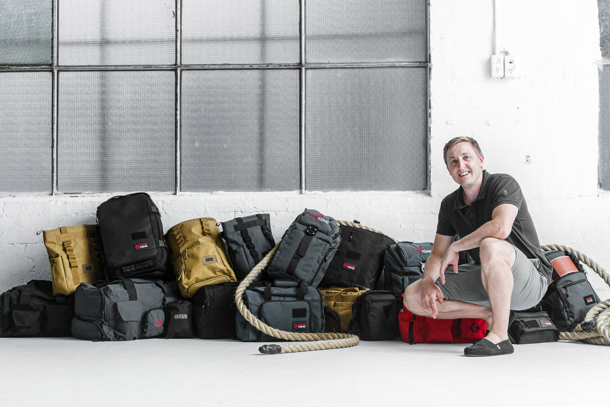 Founder of King Kong Apparel, Stefan Gehrig in a polo shirt and shorts backdropped by various bags made by his brand.