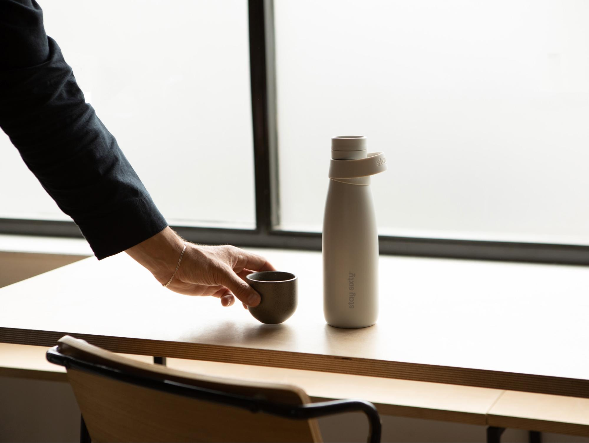A hand holding a mug backdropped by a stone colored water bottle by Stay Sixty.