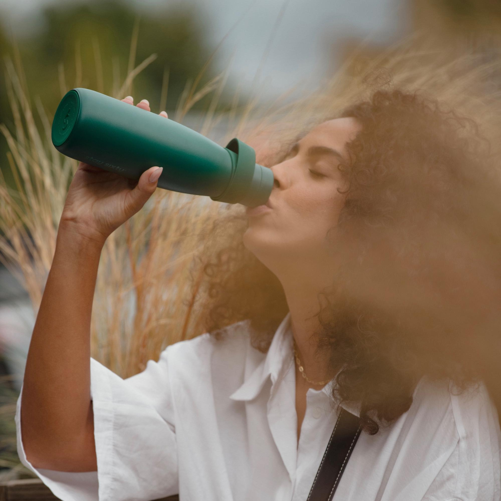 A model using an emerald water bottle from Stay Sixty.