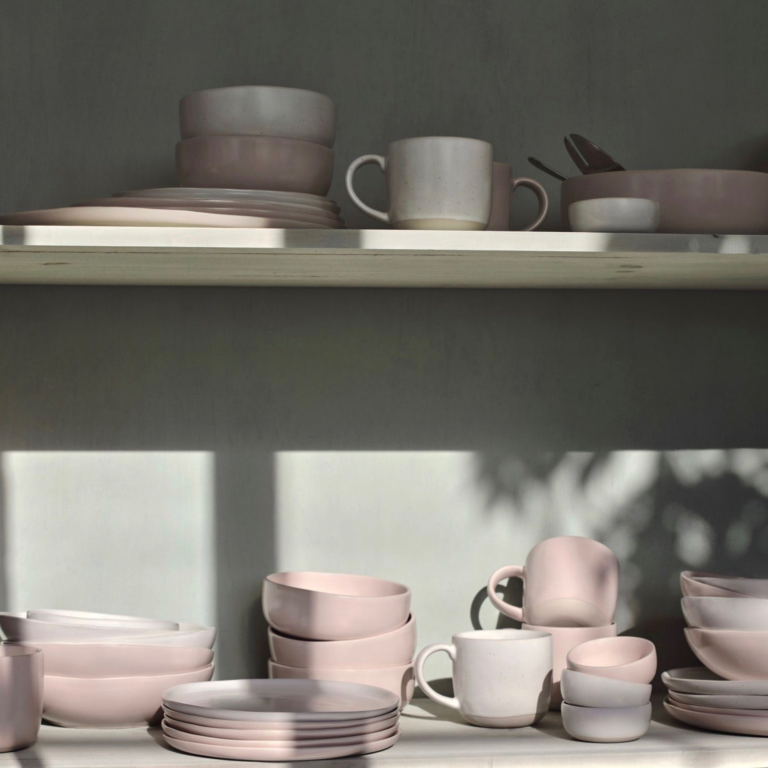 A shelf full of blush pink and speckled white dinnerware from Fable.