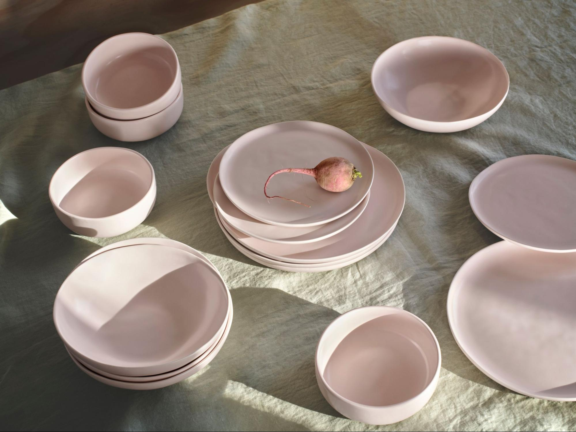 An array of blush pink dinnerware by Fable backdropped a linen tablecloth.