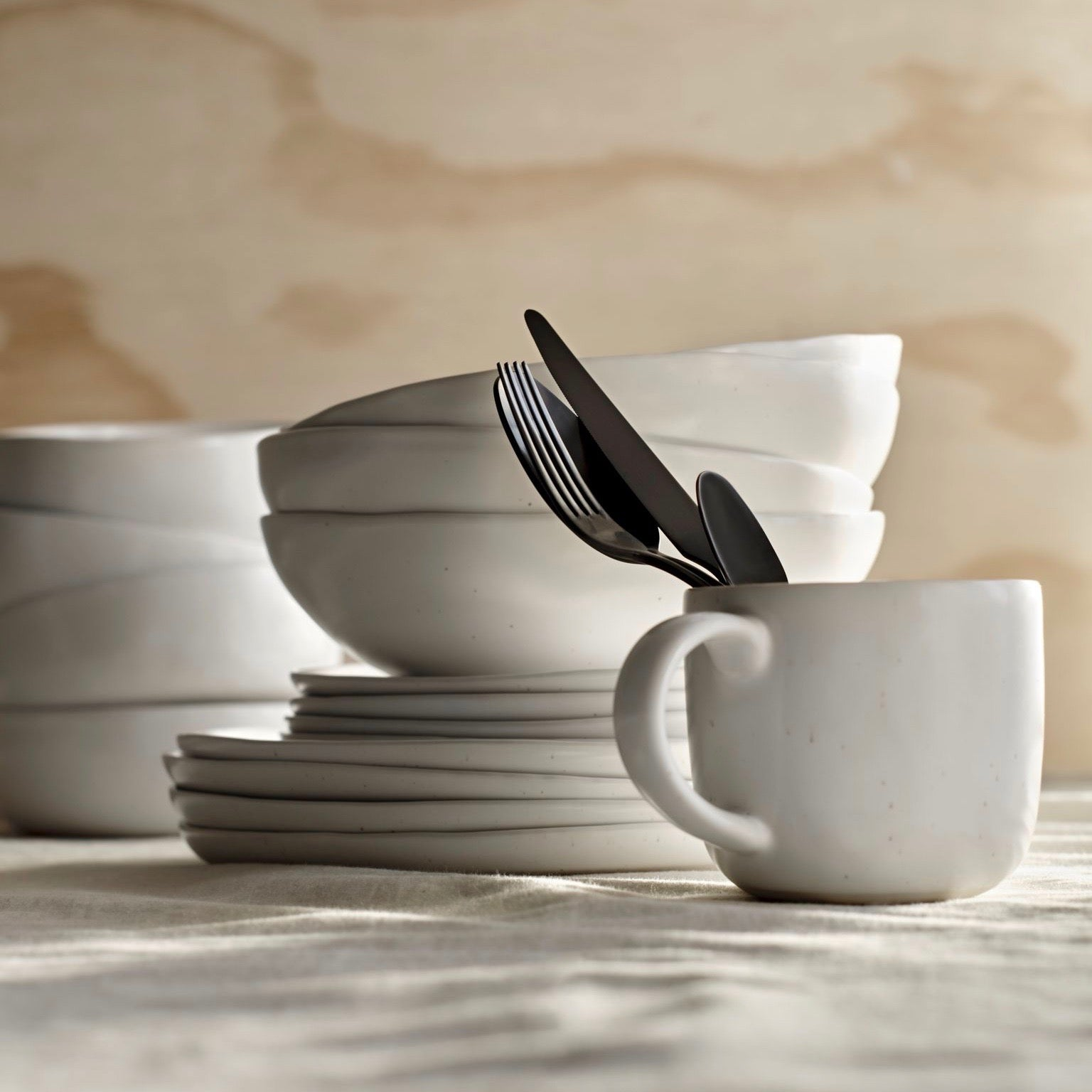 A stack of speckled white plates and bowls in the background of a mug stacked with some flatware.
