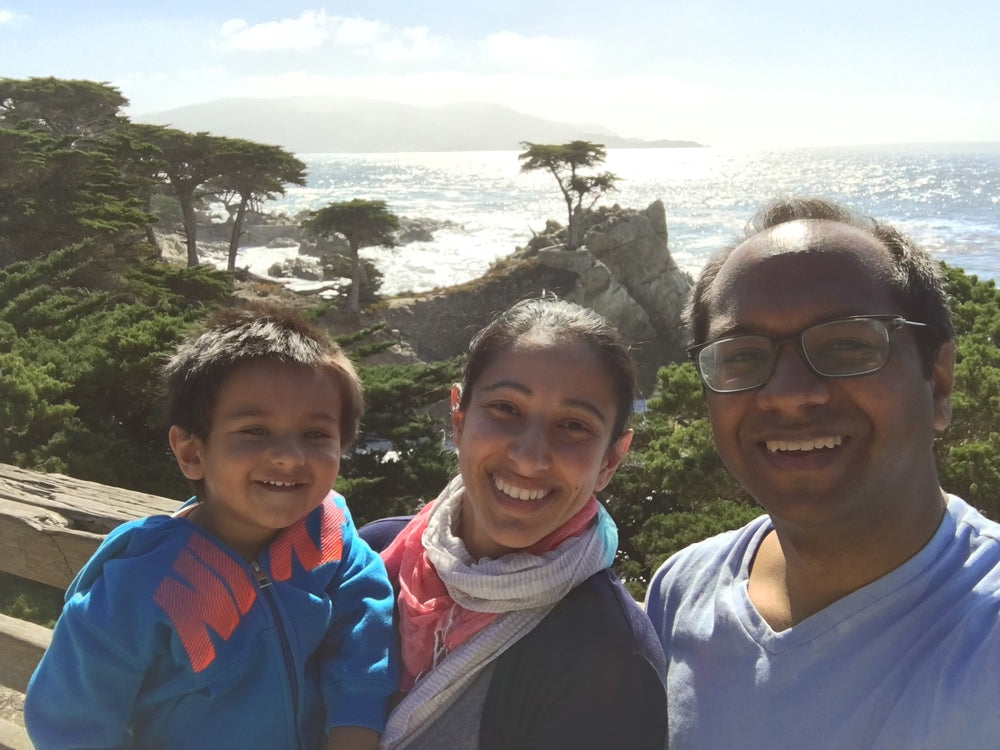 Aneela Idnani Kumar and Sameer Kumar, the life and business partners behind HabitAware along with their son backdropped by the ocean.