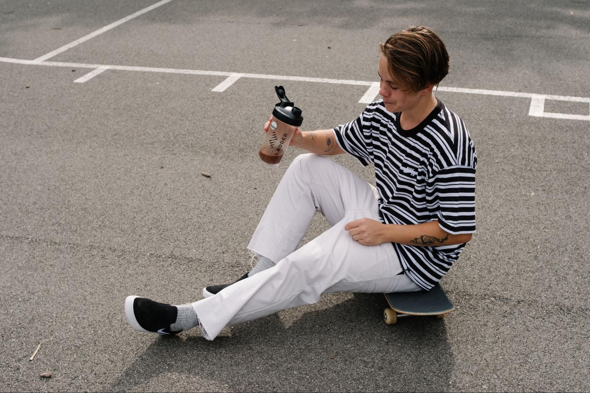 A model sits on a skateboard while drinking Ladder supplements.