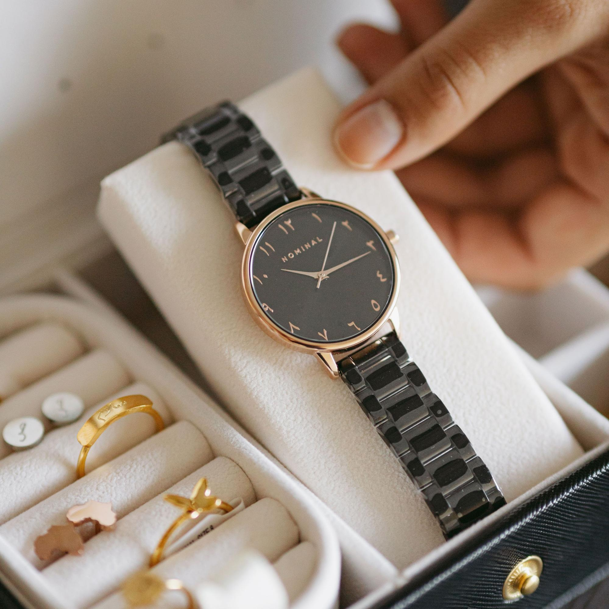 A watch, rings, and earrings in a jewelry box.