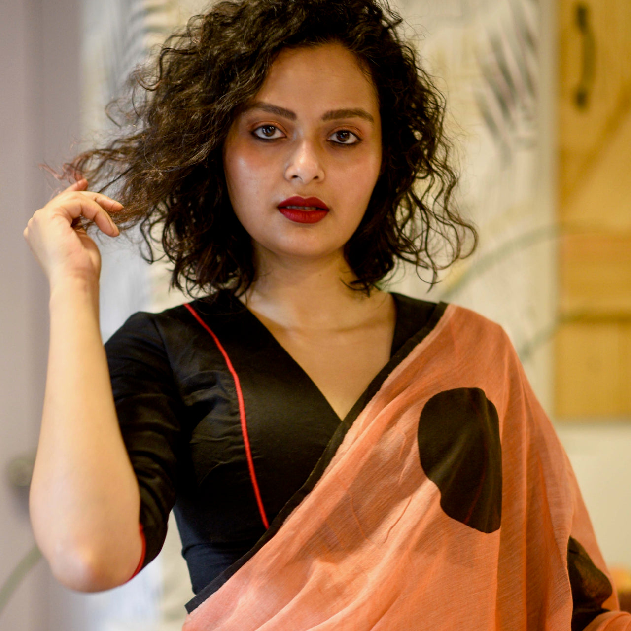 Sujata models a black blouse along with an orange saree with large black dots.