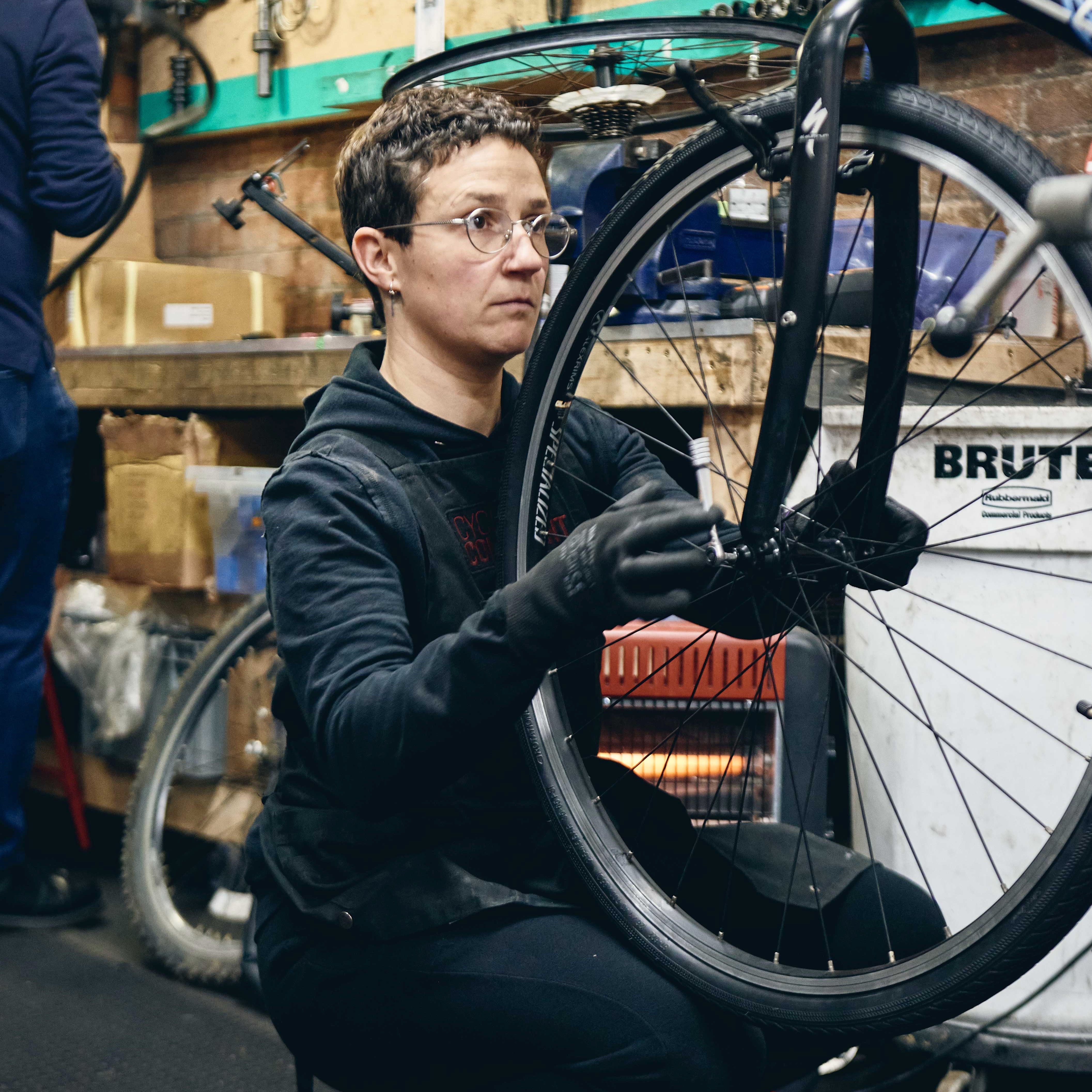 A mechanic fixing up a bike in The Bike Project's workshop.
