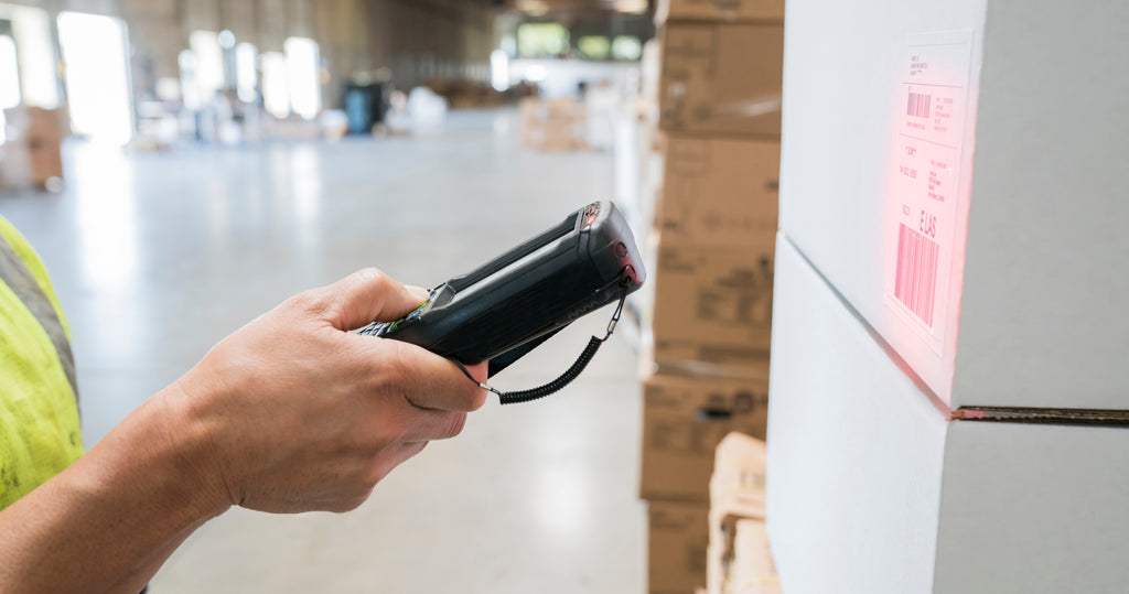 close up photo of a shipping label being scanned in a large warehouse