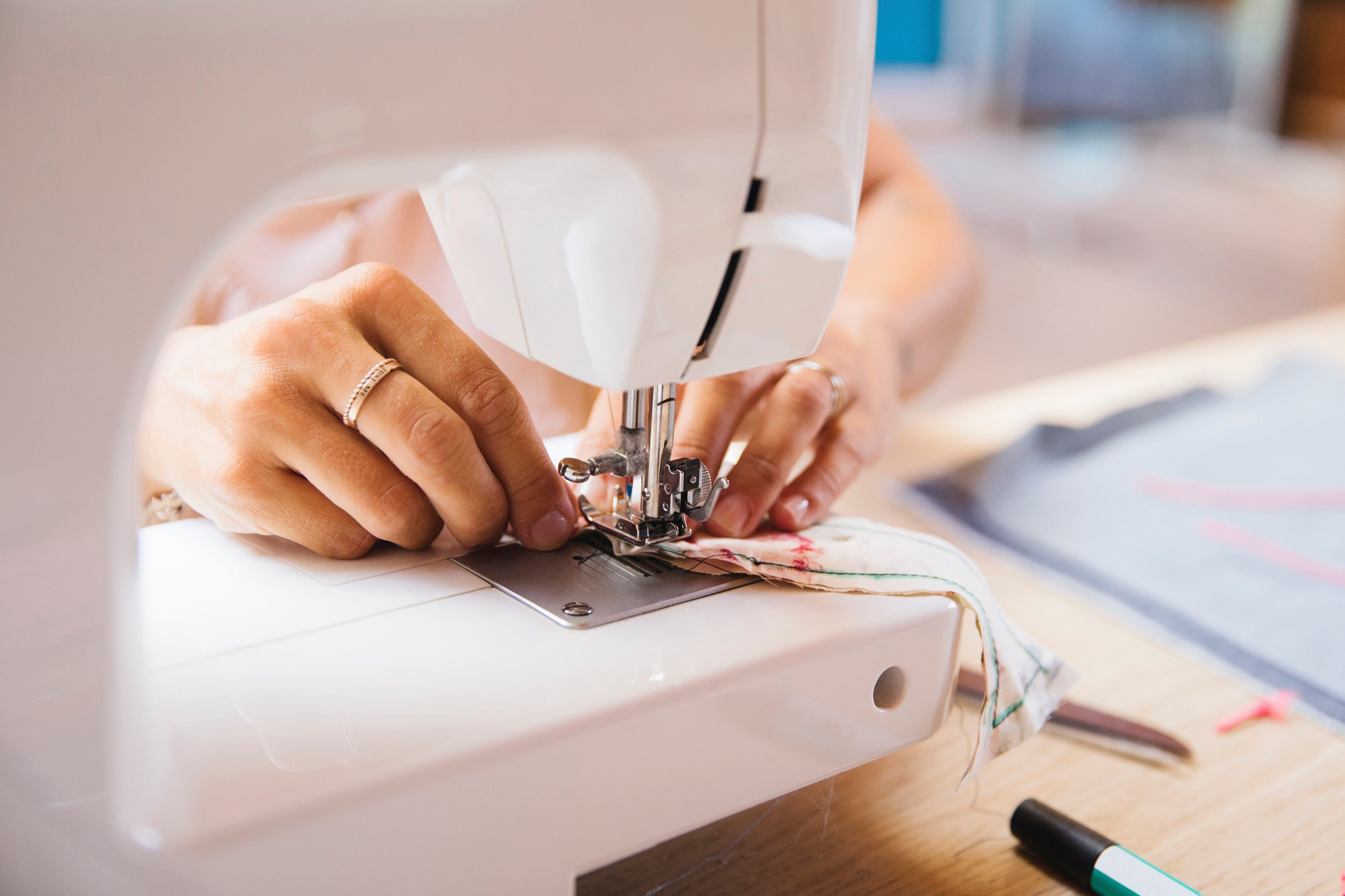Close up of female hands using a sewing machine