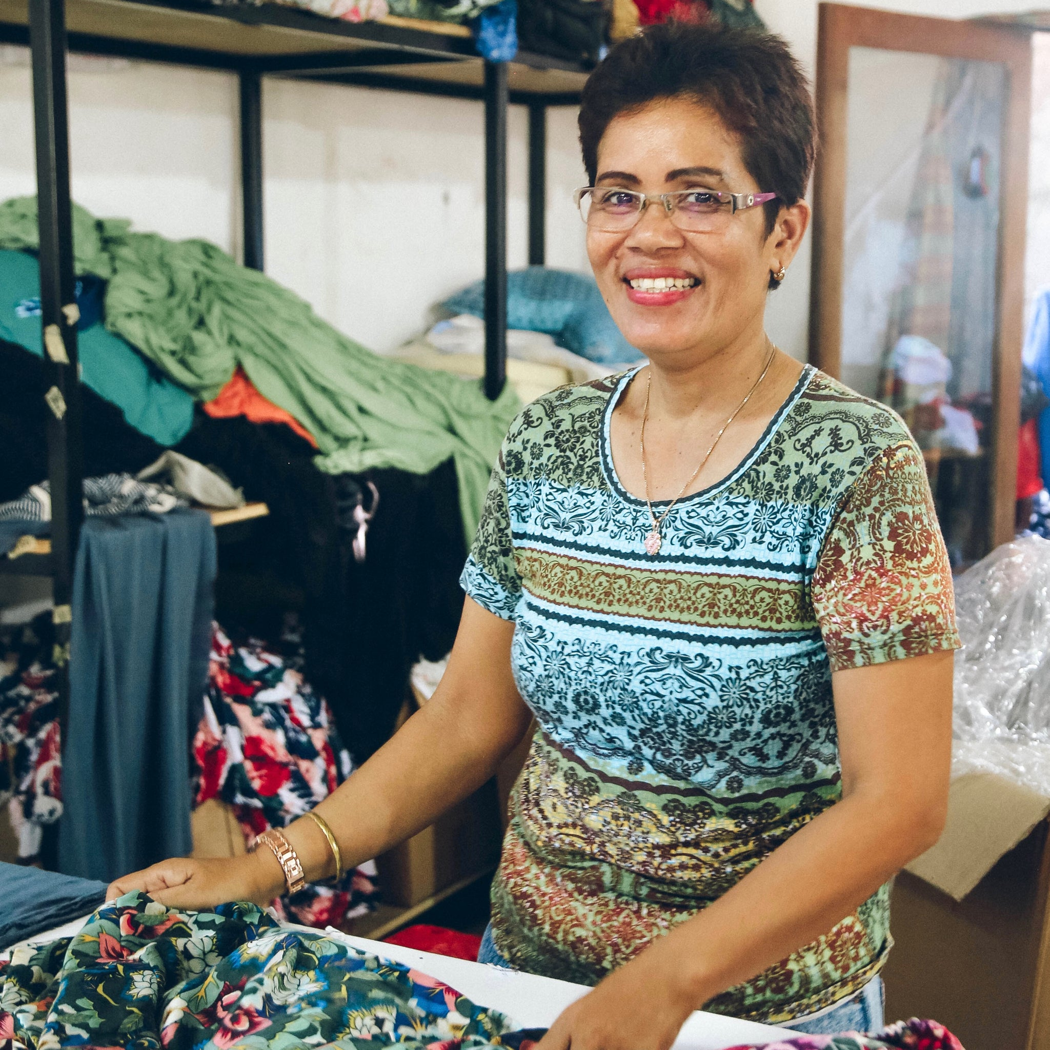 A garment worker in a production facility of TAMGA Designs.
