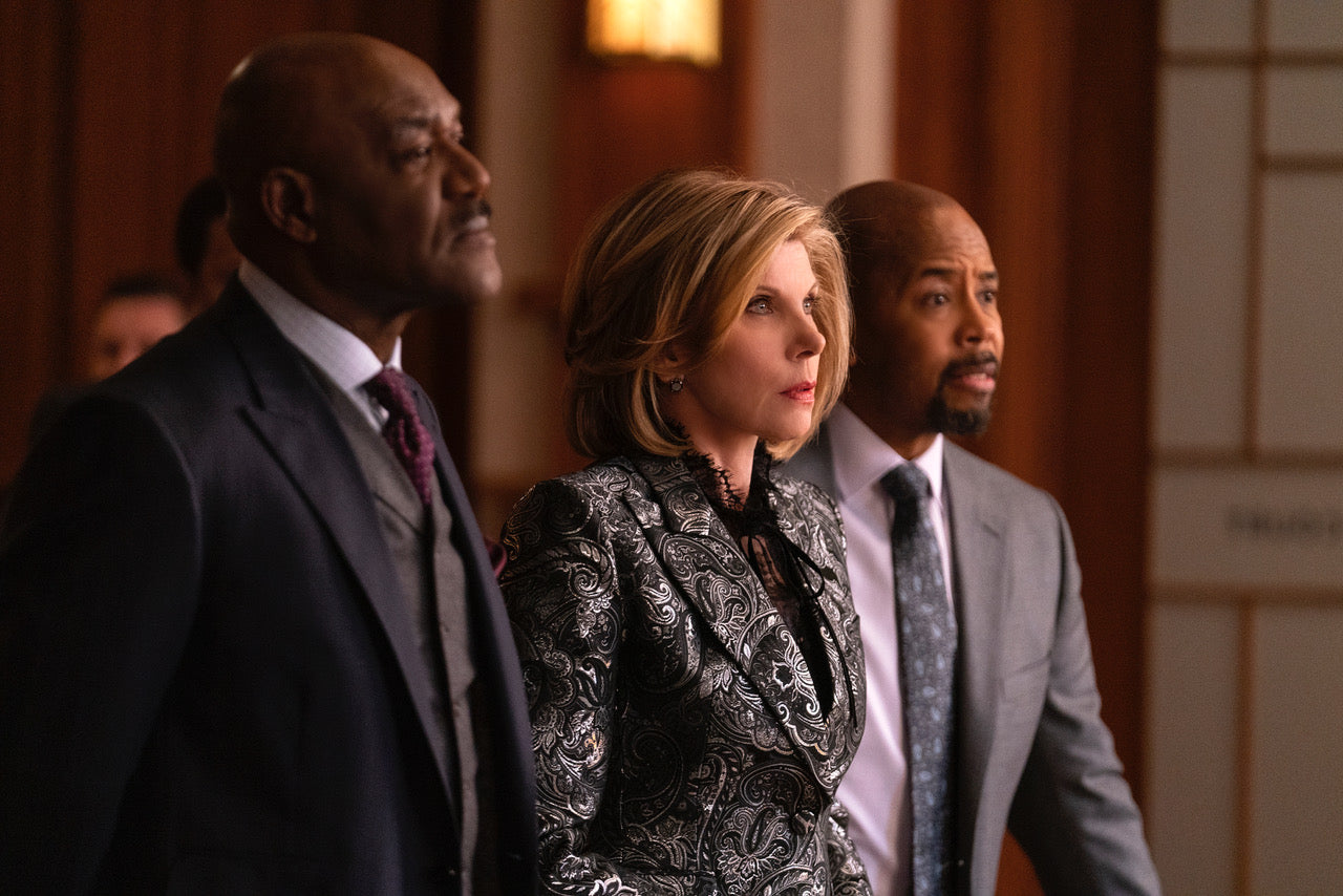 Christine Baranski from The Good Fight standing in a courtroom with a worried look on her face while two male lawyers stand on either side of her.
