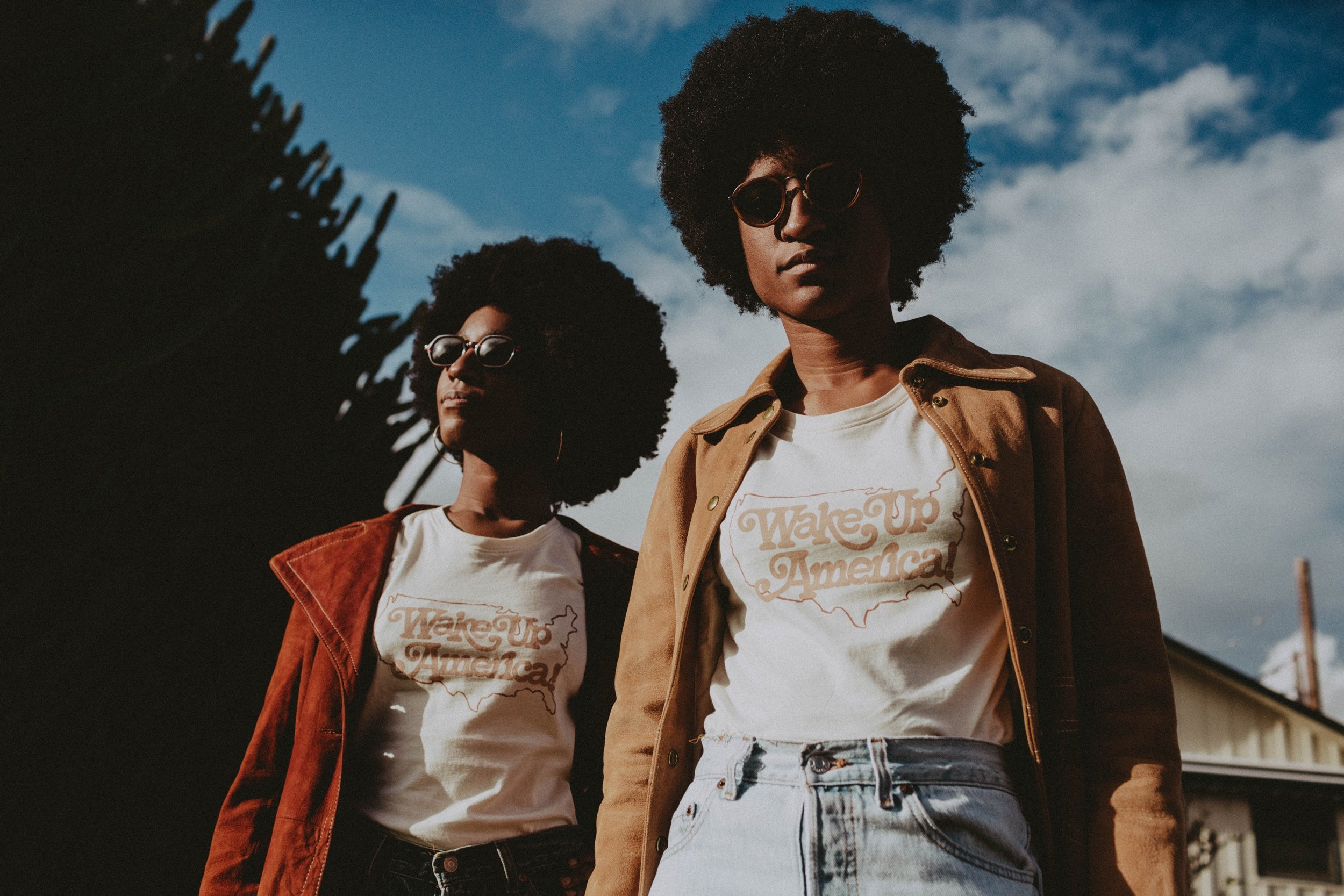 Image of a two models wearing coats and sunglasses against a sky background