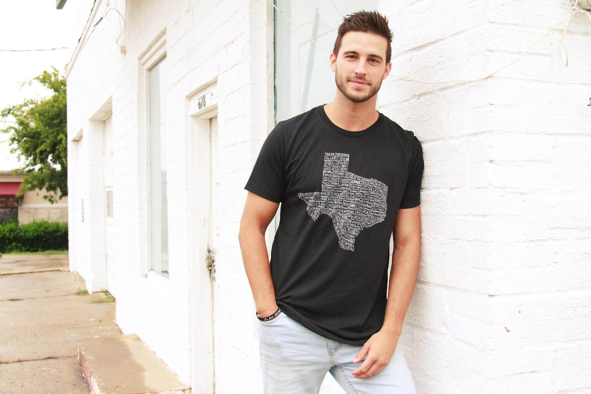 A male model in a black Tumbleweed Texstyles shirt.