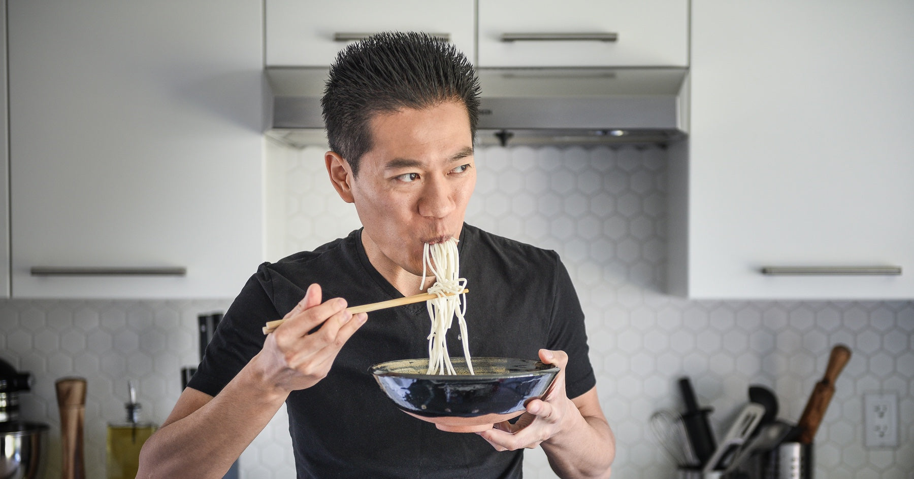 Portrait of Wil Yeung, YouTube chef and serial entrepreneur, eating a bowl of noodles