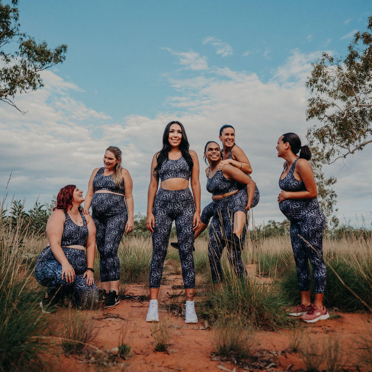 A group six women in various life stages wearing the same workout outfit by Active Truth in a dessert setting.