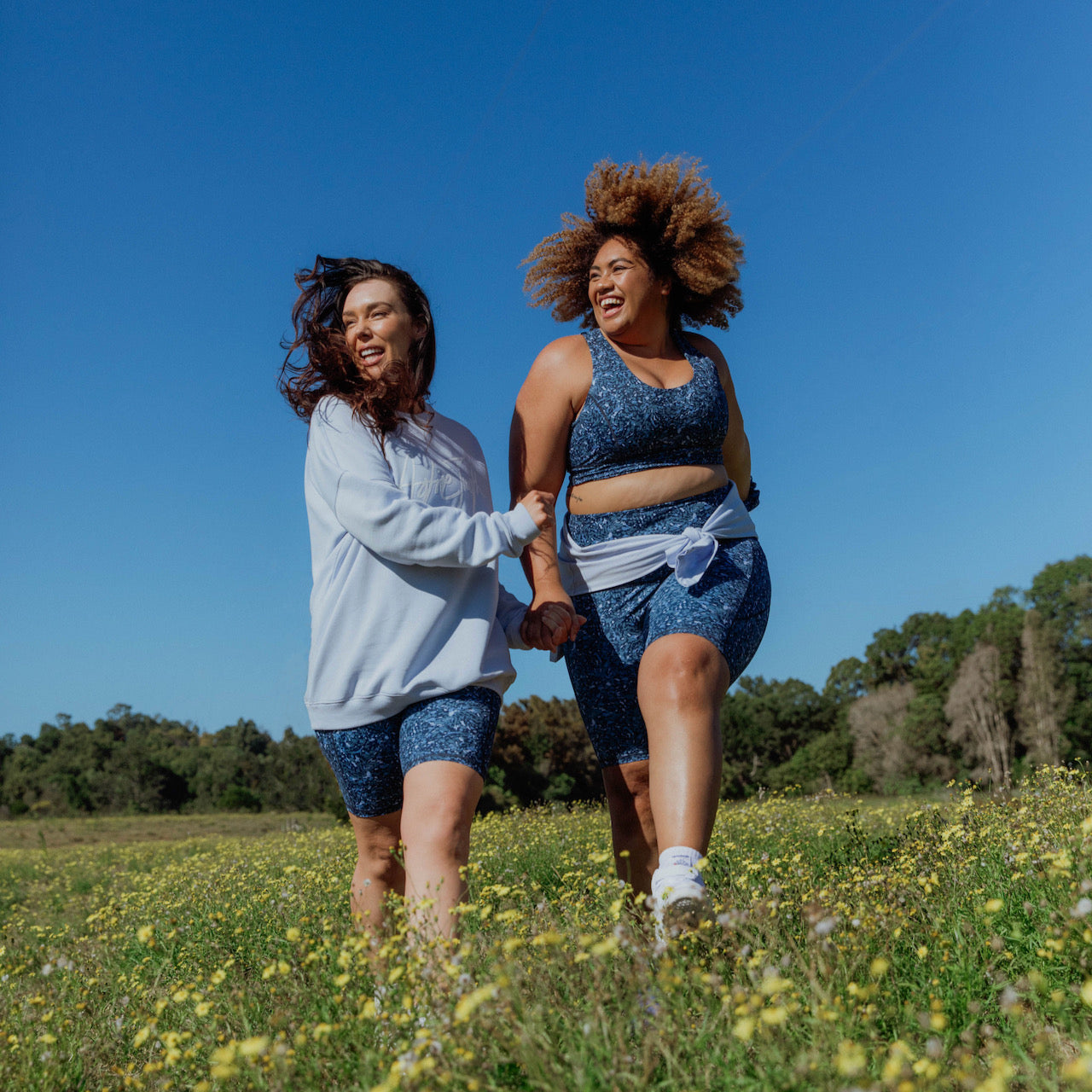 Two models in a field wearing clothes from Active Truth.