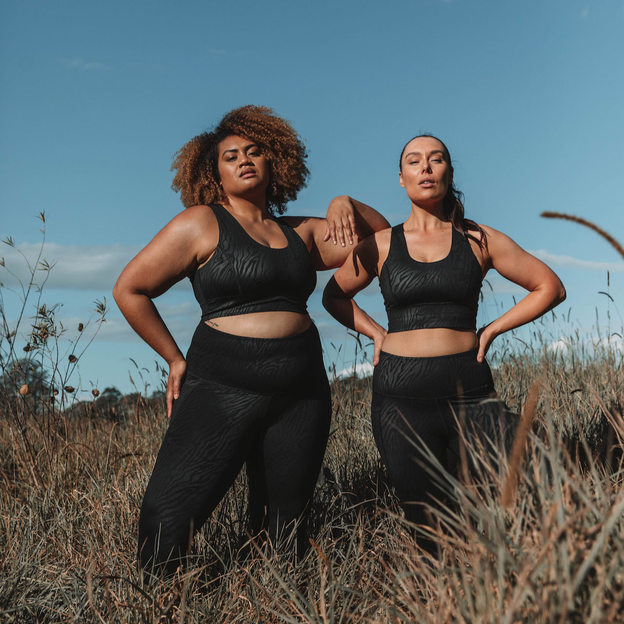 Two models wearing black workout sets from Active Truth in a field setting.