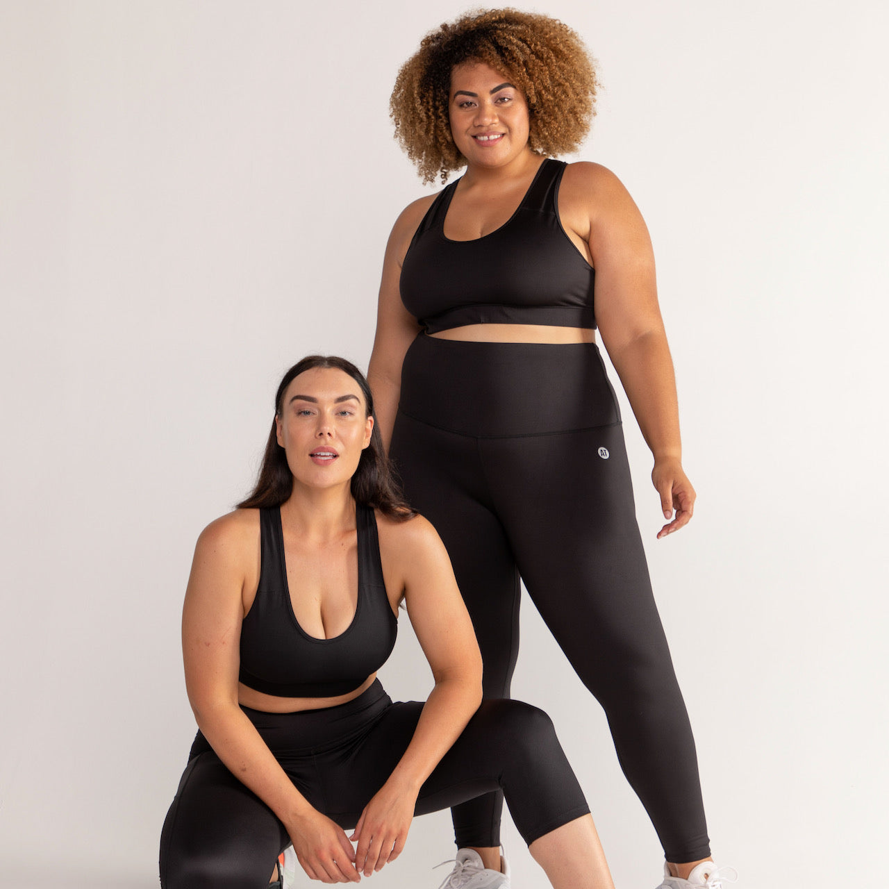 A pair of models in black workout sets by Active Truth against a white background.