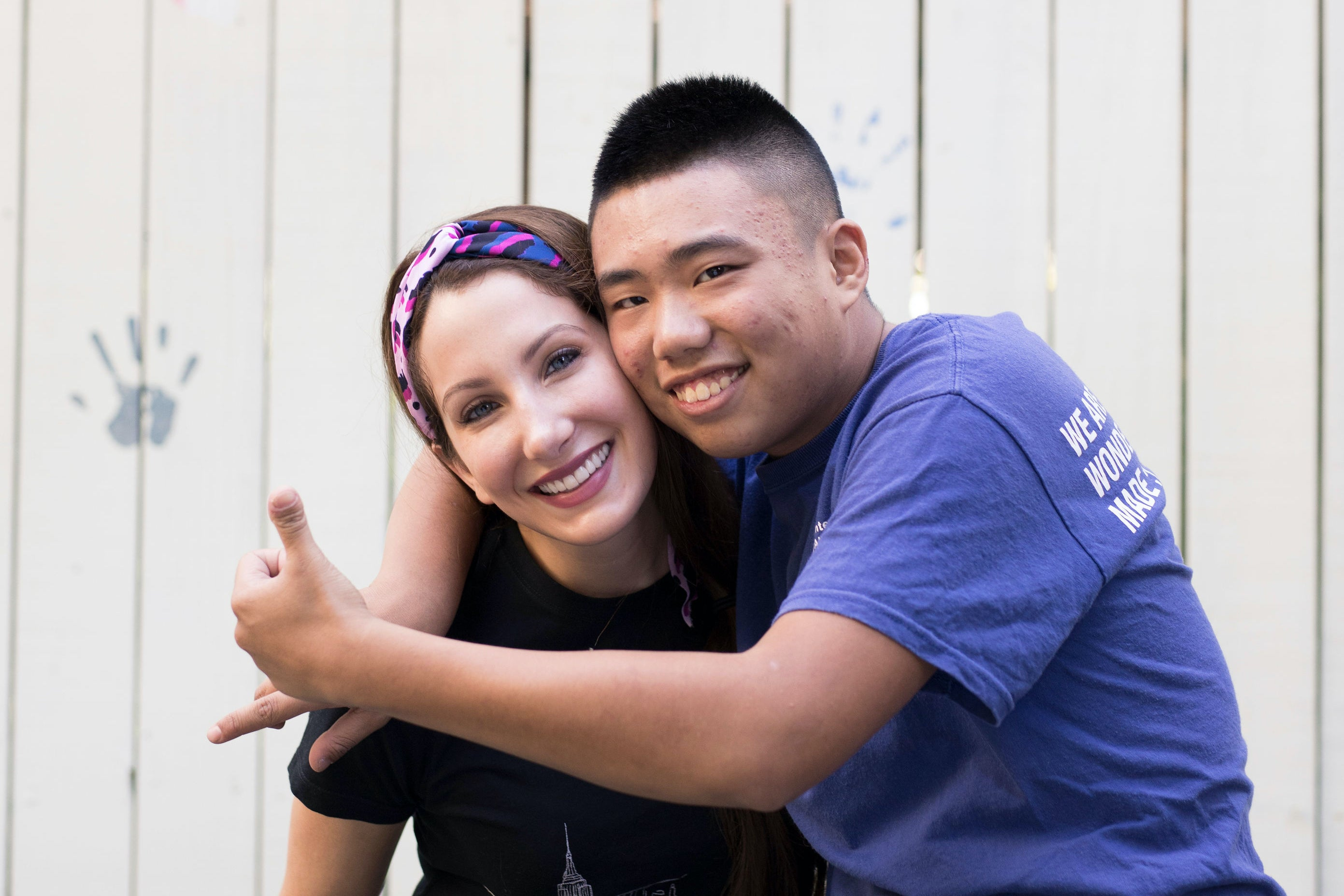 A woman is embraced by a young man who poses with thumbs up