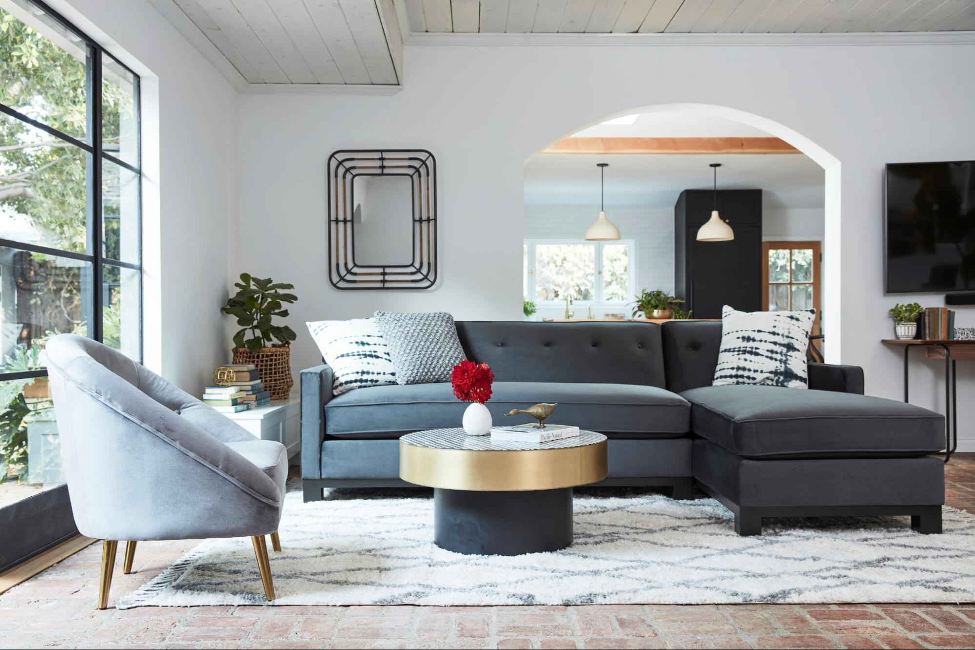 A dark grey sofa with a grey loveseat backdropped by a living room setting