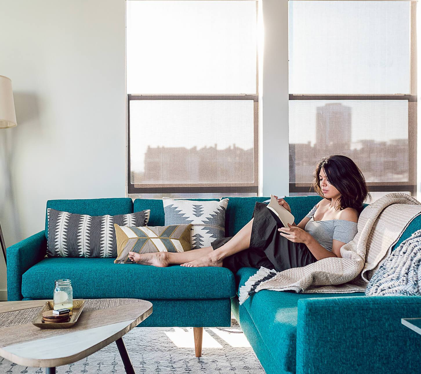 A model rests on a turquoise couch while reading a book.