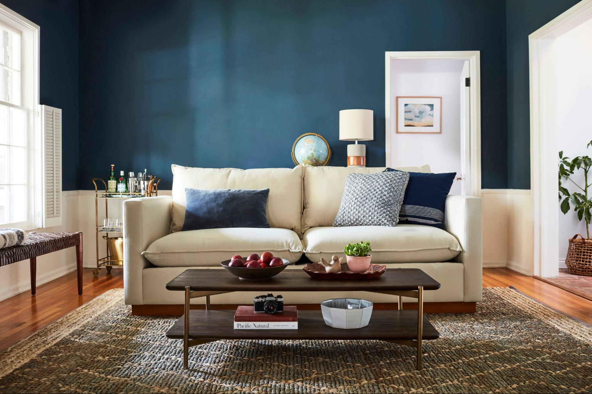 A white loveseat backdropped by a blue room complete with a coffee table and bar cart.