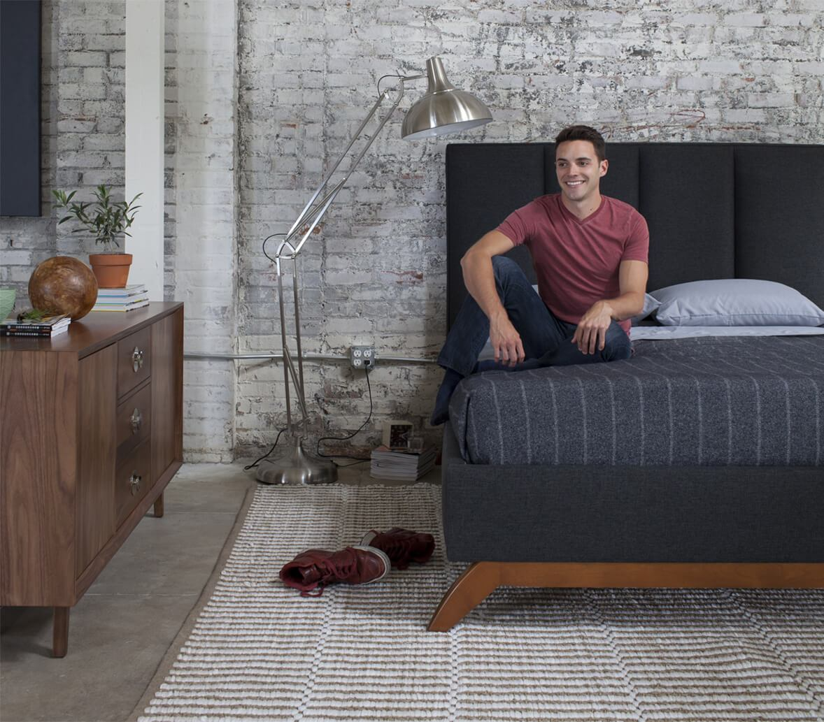 A model sits on a dark gray colored bed in a loft setting.