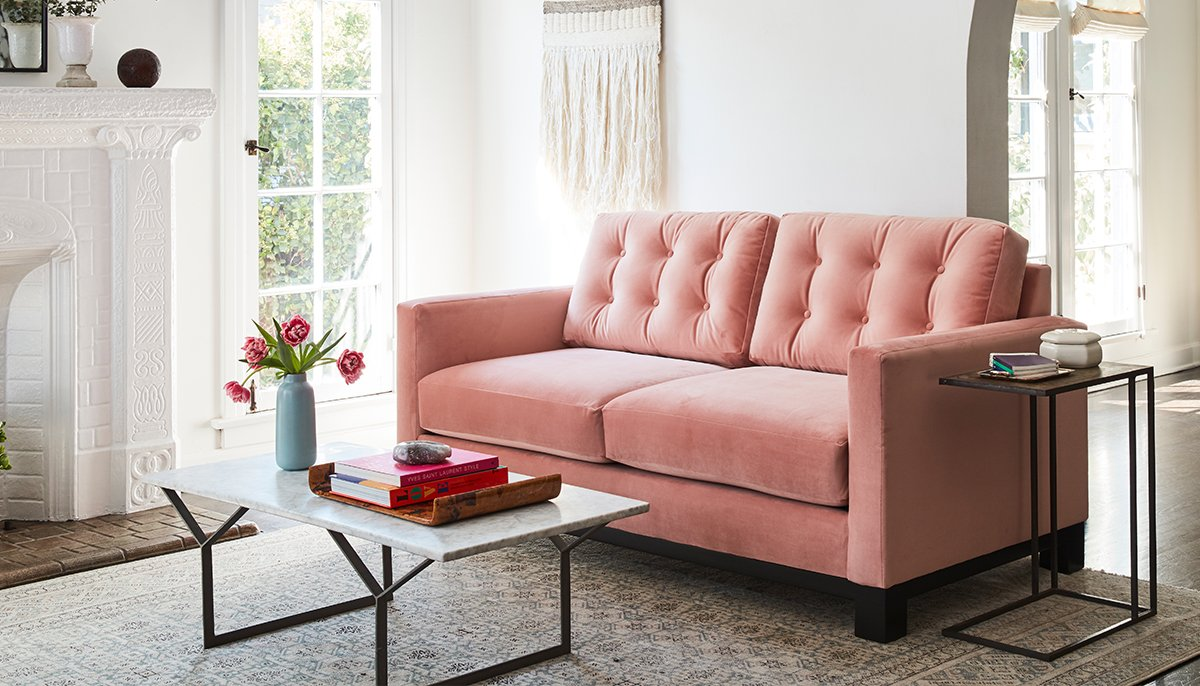 A blush colored loved seat with a marble coffee table in a living room setting.