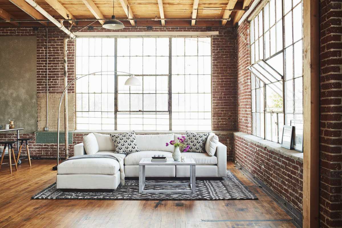 A set of white sofa in a loft setting with a coffee table and rug.