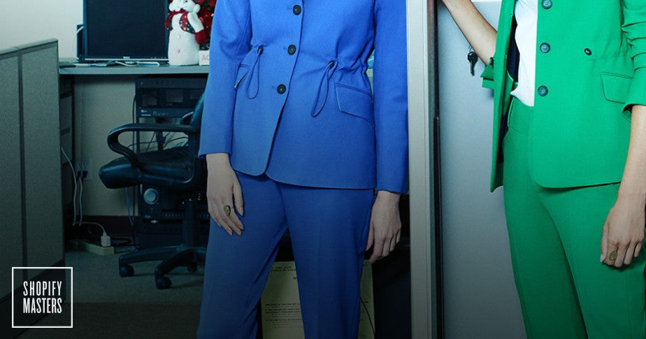 Two models posing for ARGENT, one in a blue suit, the other in a green suit.