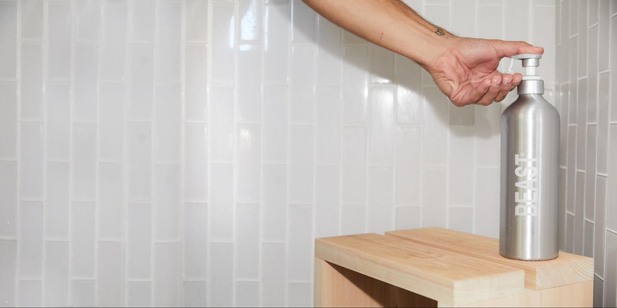 A hand in the shower using a refillable shampoo dispenser from Beast.
