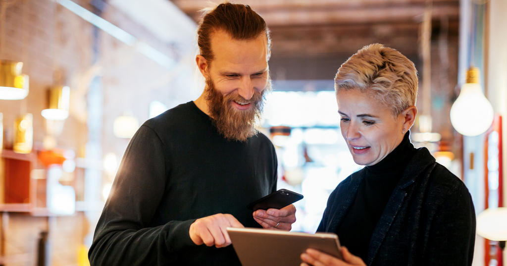 Two small business owners reviewing options for accounting software.