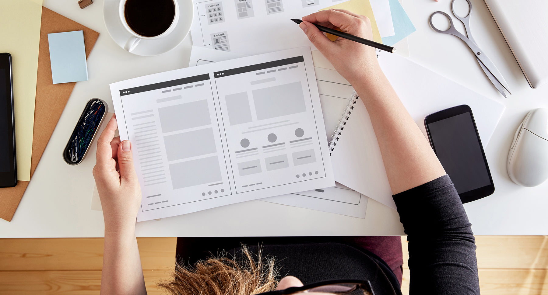 Photograph of a woman working on her website design with a sketch and prototype.