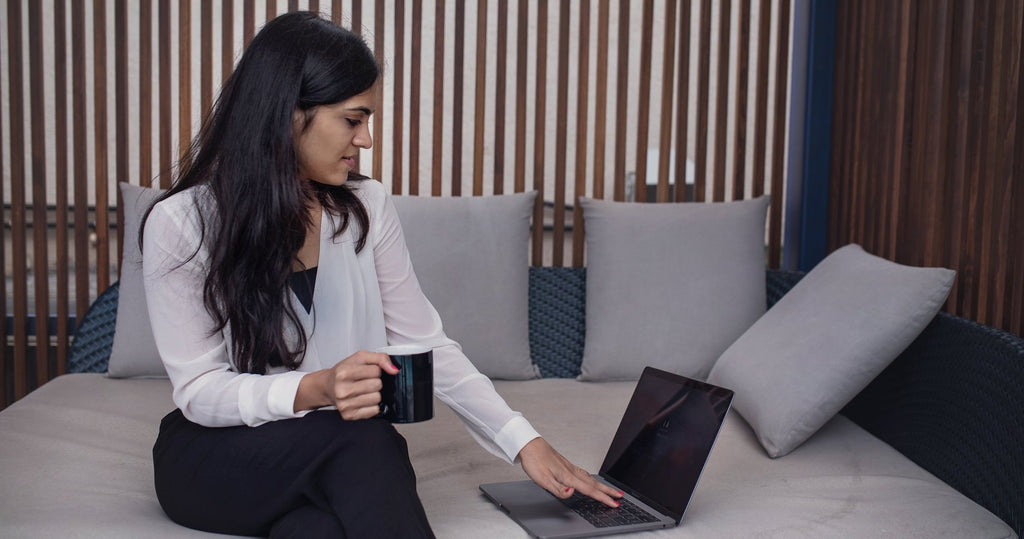 Photo of a woman sitting on her couch with a cup of coffee learning how to register a business