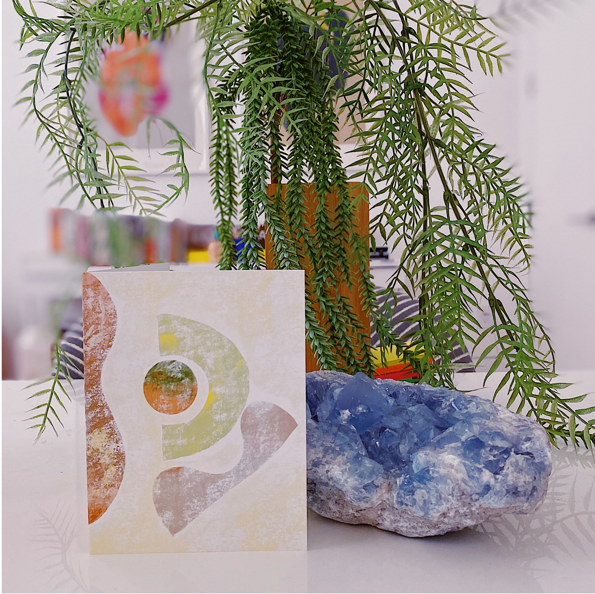 An illustrated card sits on a desk with a plant