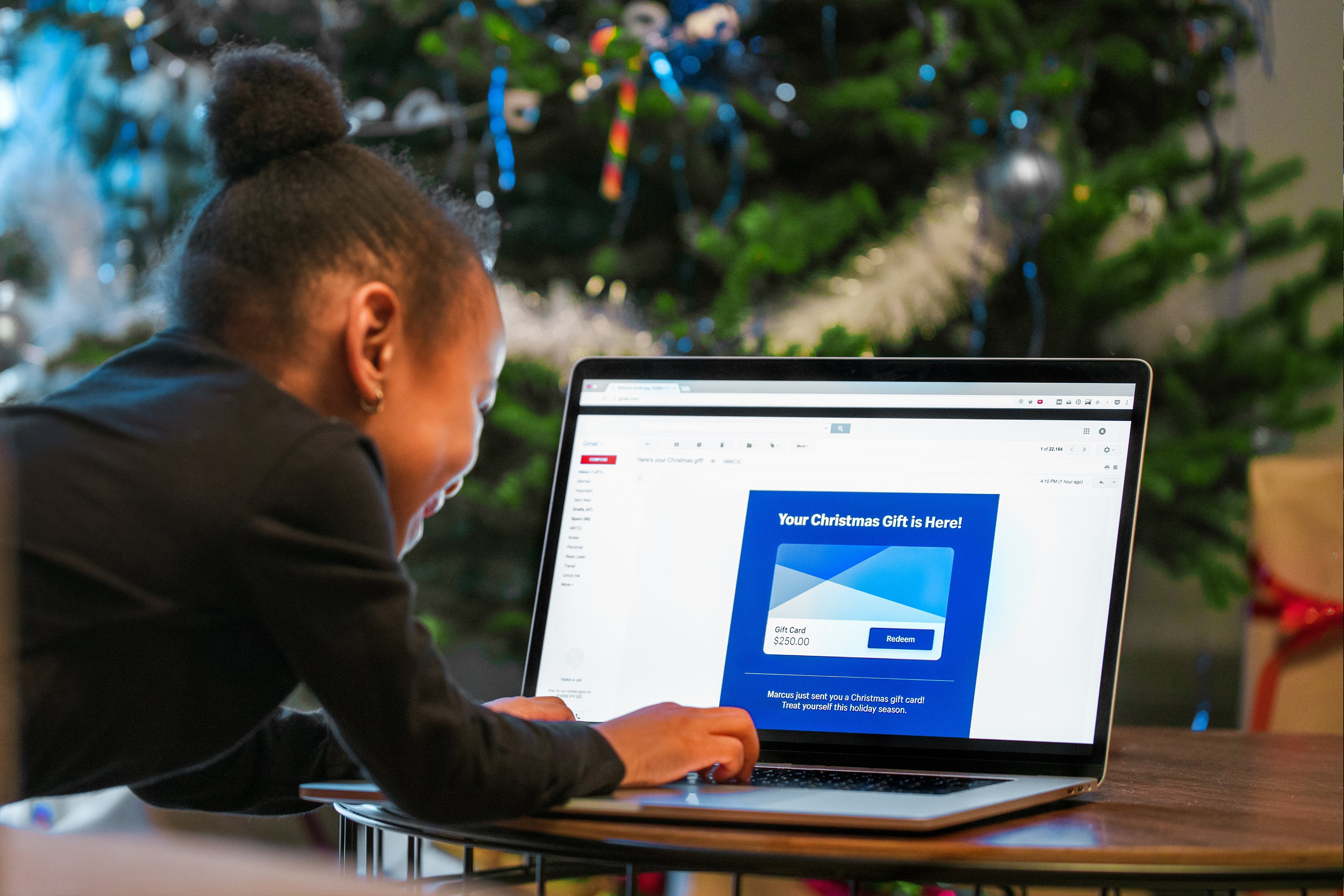 A child redeems a digital gift card online in front of the Christmas tree
