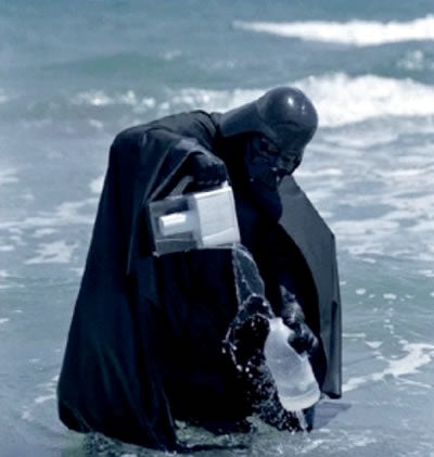 Darth Vader standing in the ocean, pouring water from a Brita pitcher into a plastic jug
