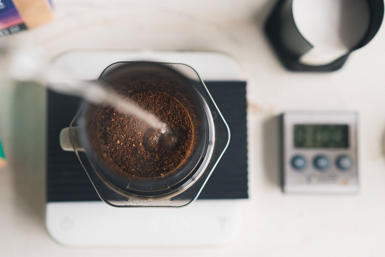 Coffee grounds are poured into a coffee maker