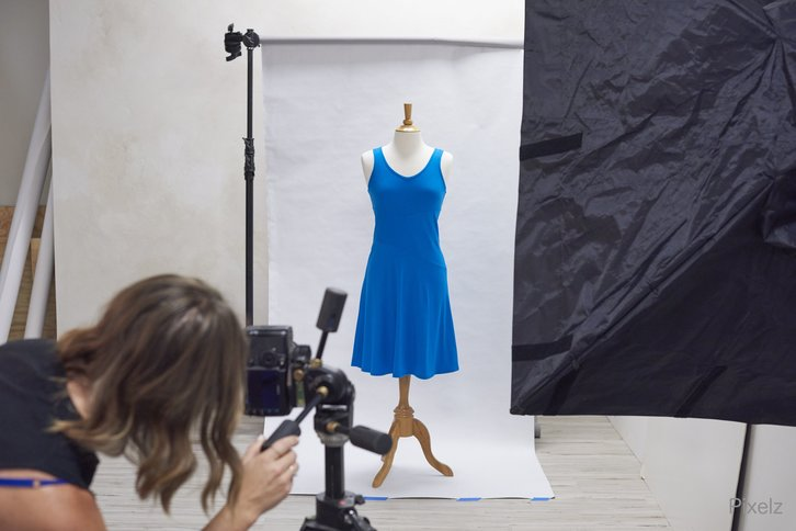Woman photographing dress.